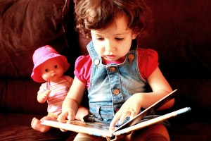 A child pretends to read a book accompanied by a doll