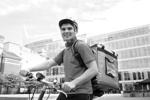 Portrait Of Courier On Bicycle Delivering Food In City