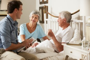 Doctor On Home Visit Discussing Health Of Senior Male Patient With Wife